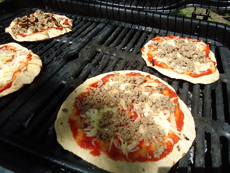 Place the topped pizzas back on the grill, close the lid, and cook ...