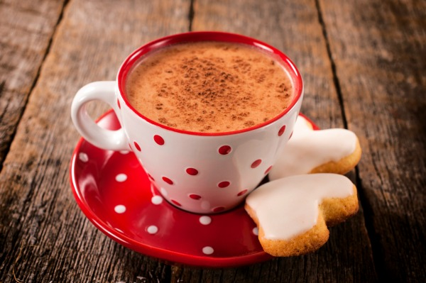 Cup of hot cocoa and heart shape cookies on wooden background